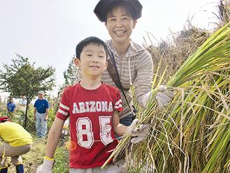 自分で刈った稲穂を手に笑顔の親子
