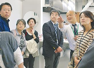 調理場で参加者に向け、説明を行う中田センター長(右から2番目)