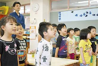 元気に歌う園児と関谷さん(写真後方)