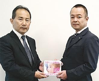 莊原さんに寄付金を手渡す中村会長(右)