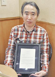 署名付きの手紙を掲げる岩永さん
