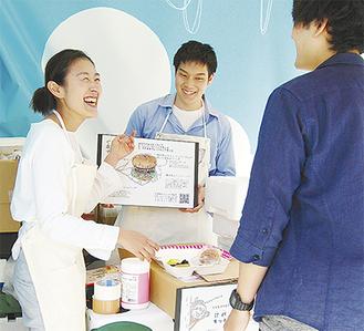来訪者に鹿肉バーガーの説明をする和賀さん(左)
