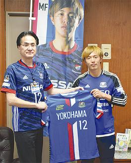 横山区長(左)にユニフォームを手渡した齋藤選手