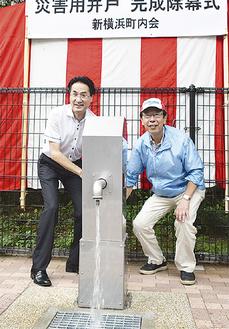 井戸の水を流す金子会長(右)と横山区長