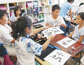習字のワークショップで和平小児童(手前)と触れ合う小机小児童