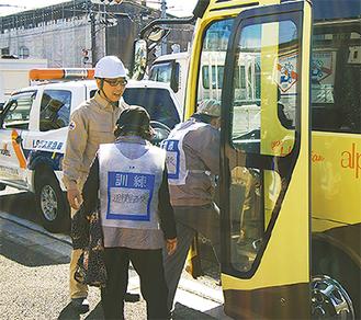 二次避難のためバスに乗り込む避難者役の参加者
