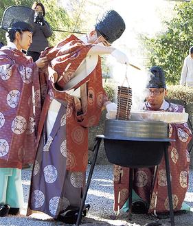 粥の入った葭の筒を釜から引き上げる石川宮司