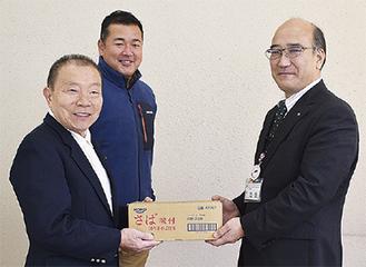 池田事務局長(右)に缶詰を手渡す篠崎会長(左)