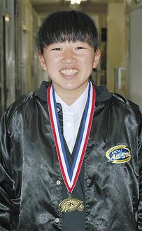 メダルを胸に笑顔を見せる松村さん