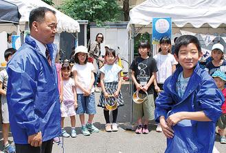 大倉山エルム通り商店会の山田浩之会長(手前左)から「会長」の任命を受けたキッズ商店街の、原結人くん(手前右)。
