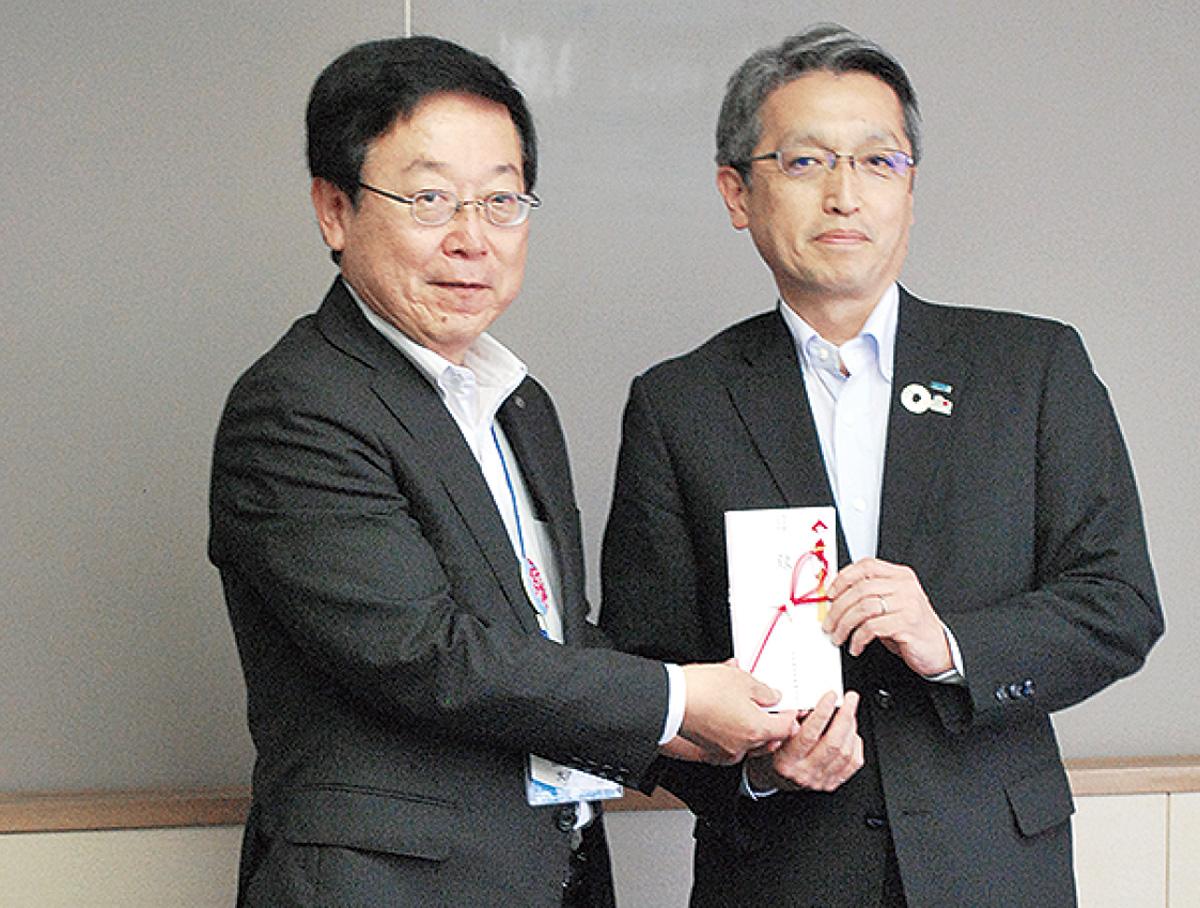 寄贈の目録を手にする鈴木支店長(右)と大八木理事長
