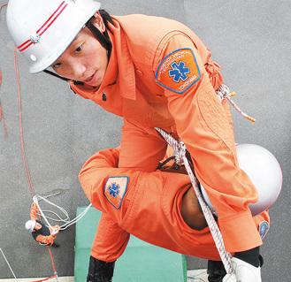 高さ7mの壁上で吊り下げ救助訓練を繰り返し行う友岡さん