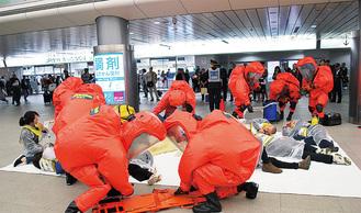 負傷者役を救助する消防士ら