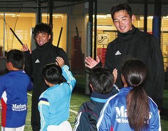 児童とハイタッチする吉尾選手(左)と原田選手
