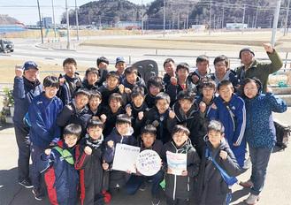 健太さんが好きだったガッツポーズで写真に納まる大豆戸フットボールクラブの子どもたち(一番左が田村孝行さん、2列目一番右が弘美さん)=クラブ提供写真