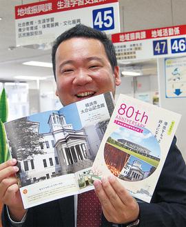 記念誌をPRする港北区役所広報相談係の小高博之さん