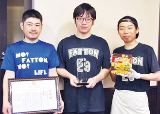 話題のカップ麺と店長(中央)とスタッフ