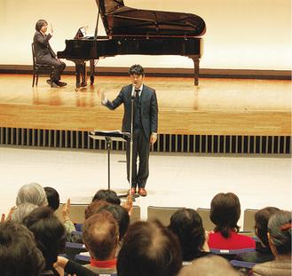 「歌う会」で指導し、聴衆を魅了する竹内氏(中央/写真は過去)