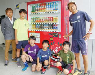 赤い自動販売機を前に笑顔の木村さん(左)、末本さん(右)と選手たち