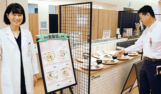 社員食堂で健康メニューをPRする島津さん(右)と保健師の坂越さん