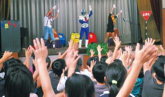 信号マン(写真中央)らと一緒に踊る児童たち