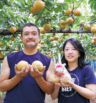 果樹園で「浜なし」を手にする憲一郎さん(左)と妻の美代子さん