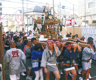 掛け声を合わせて、神輿を担ぐ住民ら(24日、宵宮祭で)