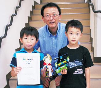 賞状を手にする赤木くん(左)とロボットを手にする横川くん(右)。中央は指導者の川原田さん