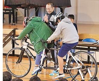原田さん(中央)とバイクを漕ぐ児童