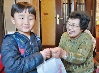 照れた表情でお菓子を買う子どもと秋山さん