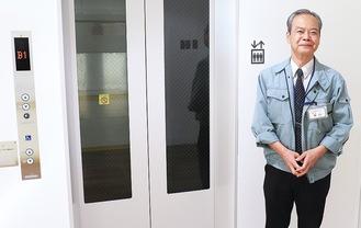 エレベーターの前に立つ関口館長