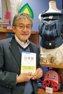 ヒット商品の1つ、抱っこ紐「エルゴベビー」の前で著書を手にする白鳥社長