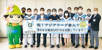 栗田るみ区長(前列左から4人目)、横浜GRITS臼井亮人代表取締役(同3人目)、浅沼芳征監督(後列左から3人目)と選手・スタッフら