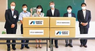 寄贈されたフェイスガードを持つ栗田区長(左から3人目)と吉田署長(同2人目)、大澤取締役(同4人目)ら