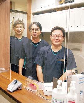 アクリル板越しに笑顔の大谷恵治院長(中央)と同院スタッフ※撮影のためマスクを外しています
