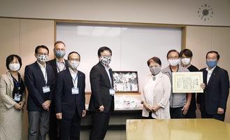 寄贈されたマスクを着ける大八木理事長(中央左)と萩生田代表(中央右)