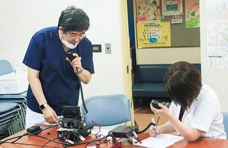 無線で指示を出す鈴木会長(左)