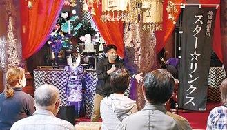 本堂に飾られた甲冑の前で語る松井さん