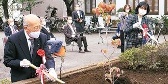 植樹を行う栗田区長(奥)と飯山代表理事(手前)