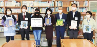 寄贈されたボードを手にする安達さん(左から3人目)と栗田区長(同4人目)ら