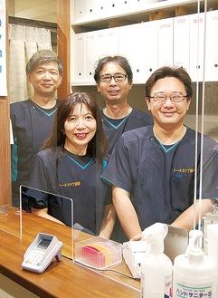 アクリル板越しに笑顔の大谷恵治院長(後列右)と同院スタッフ※撮影のためマスクを外しています