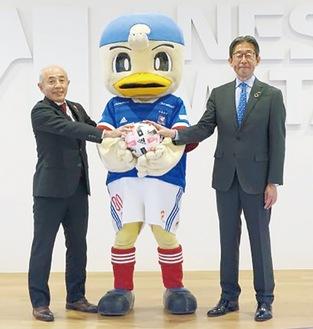 マリノスケを挟んで笑顔を見せる黒澤良二氏(左)と壷田貴弘氏