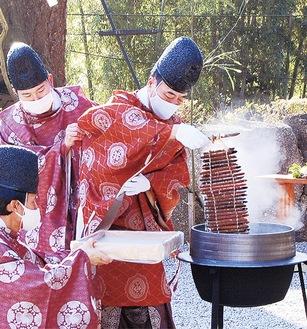 大釡から粥の入った葭の筒を引き上げる石川宮司
