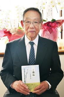 著書を手に笑顔の小木田さん