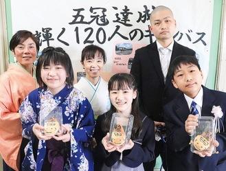 しんよしだくんパンを手に笑顔を見せる児童らと関谷校長(後列中央)