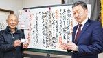 住民カードを手にする奈良さん(右)と秋本会長