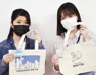 自身のデザインをあしらったグッズを手にする井上さん(左)と松尾さん=提供写真