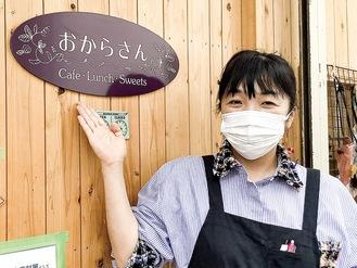 カフェおからさんの前で「お気軽にご相談を」と話す青木理事長