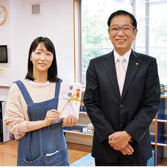 上村会長と、目録を受け取った施設スタッフ