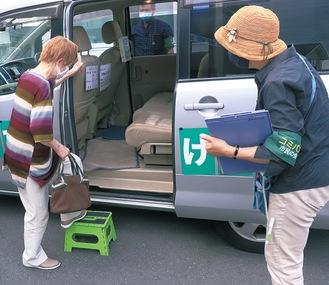 おでかけバスに乗車する利用者と砂田さん(右)